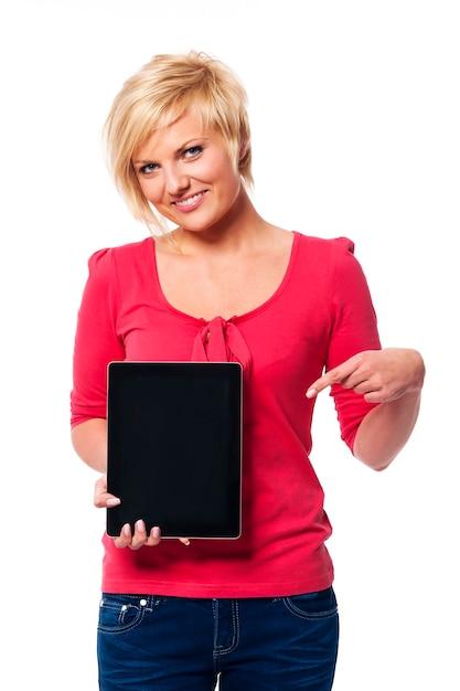 Lächelnde blonde frau, die auf bildschirm des digitalen tabletts zeigt Kostenlose Fotos