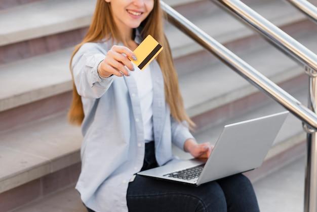 Lächelnde blonde frau, die eine kreditkarte zeigt Kostenlose Fotos
