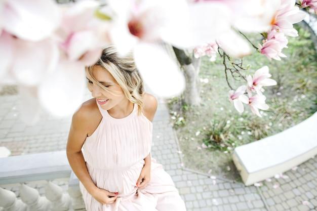 Lächelnde blonde frau im kleid, das unter dem baum sitzt Kostenlose Fotos