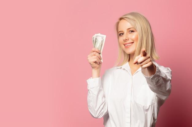 Lächelnde blonde frau mit dollarbargeld Premium Fotos