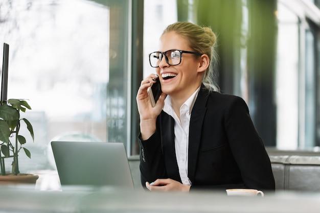 Lächelnde blonde geschäftsfrau, die mit dem handy spricht Kostenlose Fotos