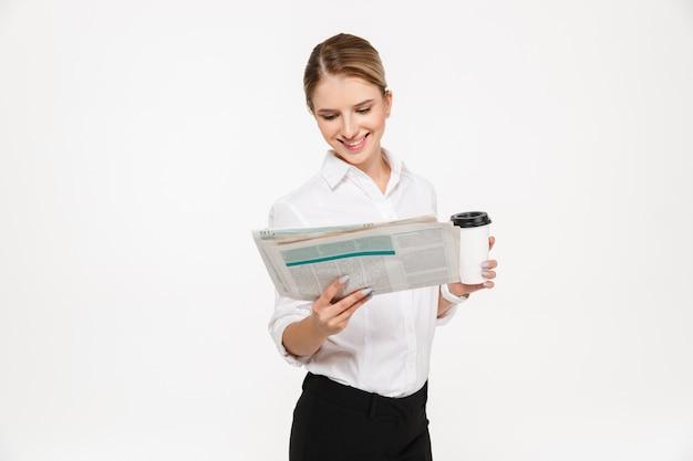 Lächelnde blonde geschäftsfrau, die zeitung liest, während tasse kaffee über weißer wand hält Kostenlose Fotos