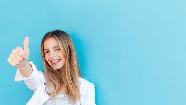 Lächelnde blonde junge frau, die daumen herauf zeichen gegen blauen hintergrund zeigt Premium Fotos