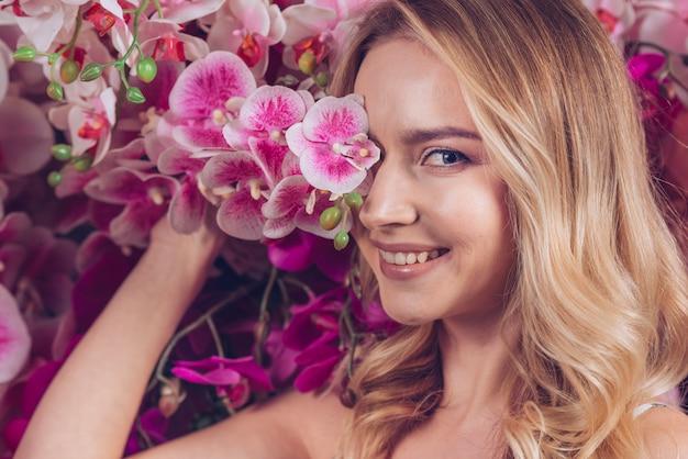 Lächelnde blonde junge frau, die ihre einen augen mit rosa orchideenniederlassung bedeckt Kostenlose Fotos
