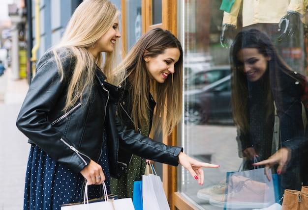 Lächelnde blonde junge frau, die ihren freund zeigt auf schuhe in der fensteranzeige betrachtet Kostenlose Fotos