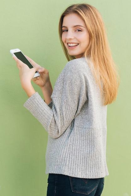 Lächelnde blonde junge frau, die in der hand handy gegen grünen hintergrund hält Kostenlose Fotos