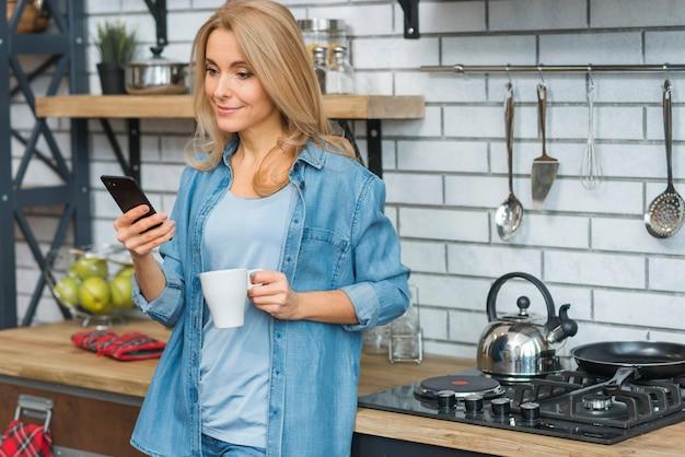 Lächelnde blonde junge frau, die tasse kaffee betrachtet handy hält Kostenlose Fotos