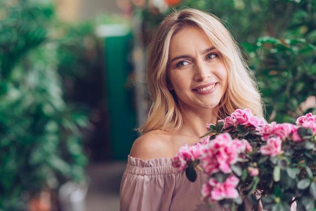 Lächelnde blonde junge frau, die vor blühenden pflanzen steht Kostenlose Fotos
