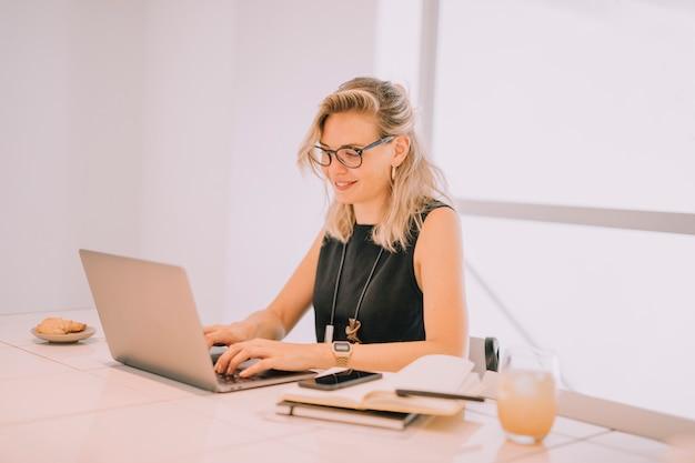 Lächelnde blonde junge geschäftsfrau, die laptop mit frühstück auf bürotisch verwendet Kostenlose Fotos