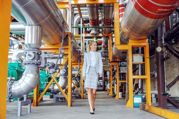 Lächelnde blonde kraftwerksbesitzerin, die herumläuft und maschinen überprüft. Premium Fotos