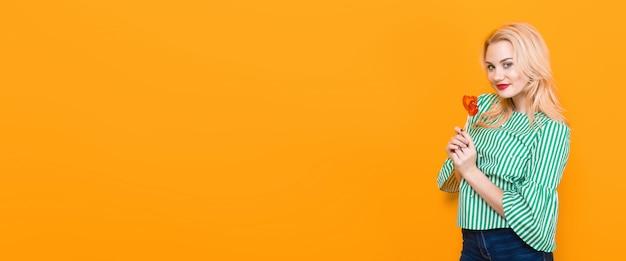 Lächelnde blondine halten herzförmige lutscher, hintergrund Premium Fotos