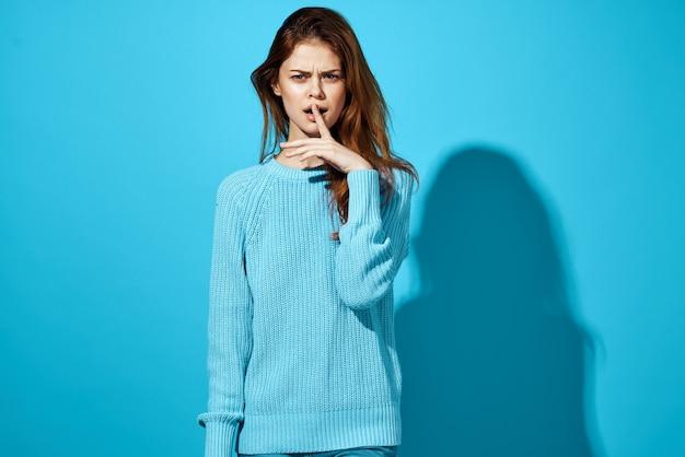 Lächelnde brünette im blauen pullover und in den jeansemotionen beschnittene ansicht isolierten hintergrund. hochwertiges foto Premium Fotos