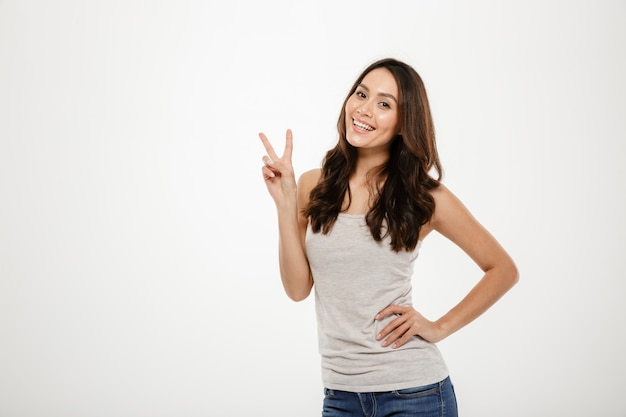 Lächelnde brunettefrau mit dem arm auf der hüfte, die friedensgeste zeigt und die kamera über grau betrachtet Kostenlose Fotos