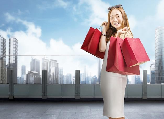 Lächelnde chinesische frau, die rote einkaufstaschen auf dem mall hält Premium Fotos