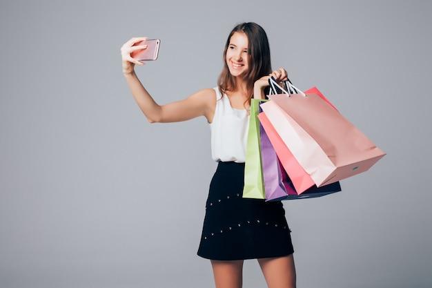 Lächelnde dame, die selfie auf ihrem telefon mit einkaufstüten auf weißem hintergrund mit papiertüten in ihren armen macht Kostenlose Fotos
