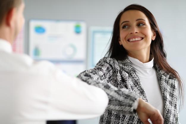 Lächelnde dame im anzug coronavirus händedruck Premium Fotos