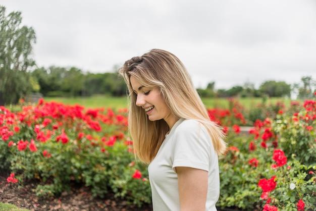 Lächelnde dame im t-shirt nahe roten blumen Kostenlose Fotos