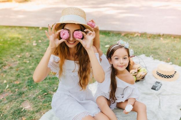 Lächelnde dame im weißen kleid hält rosa lebkuchen wie brille, sitzt auf decke mit tochter. hübsches kleines mädchen mit band, das neben scherzender mutter während des picknicks aufwirft. Kostenlose Fotos