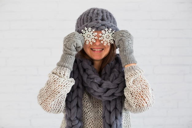 Lächelnde dame in den handschuhen, im schal und im hut mit verzierungsschneeflocken auf augen Kostenlose Fotos