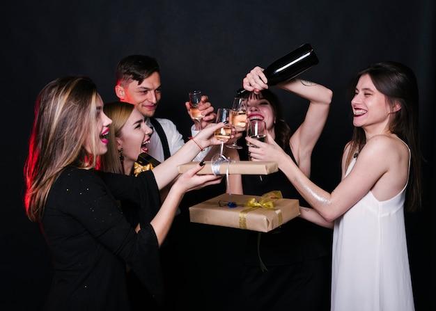 Lächelnde damen und herren in abendgarderobe mit flasche, gläsern von getränken und geschenkboxen Kostenlose Fotos