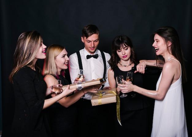 Lächelnde damen und herren in abendgarderobe mit getränken und geschenkboxen Kostenlose Fotos