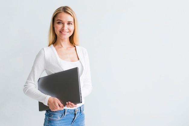 Lächelnde dünne blonde frau in den jeans mit schwarzem laptop Kostenlose Fotos