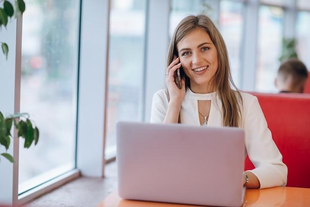 Lächelnde elegante frau am telefon zu sprechen und nach vorne schauen Kostenlose Fotos