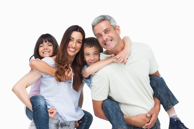 Lächelnde eltern, die ihre kinder auf rückseiten halten Premium Fotos