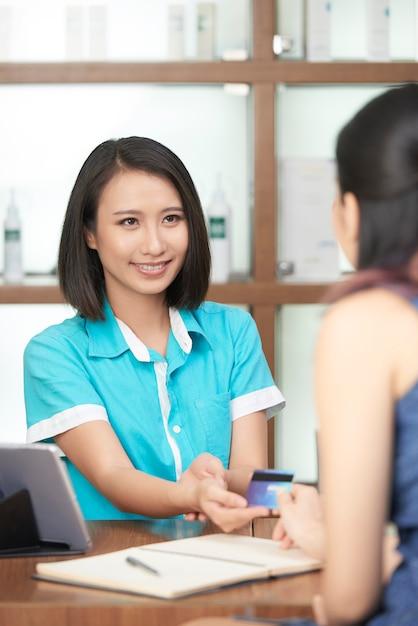 Lächelnde empfangsdame, die zahlung des kunden entgegennimmt Kostenlose Fotos