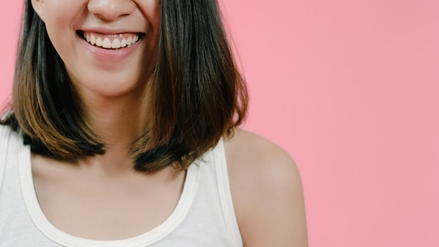 Lächelnde entzückende asiatische frau mit positivem ausdruck, lächelt breit, kleidete in der freizeitbekleidung an und betrachtete die kamera über rosa hintergrund. Kostenlose Fotos