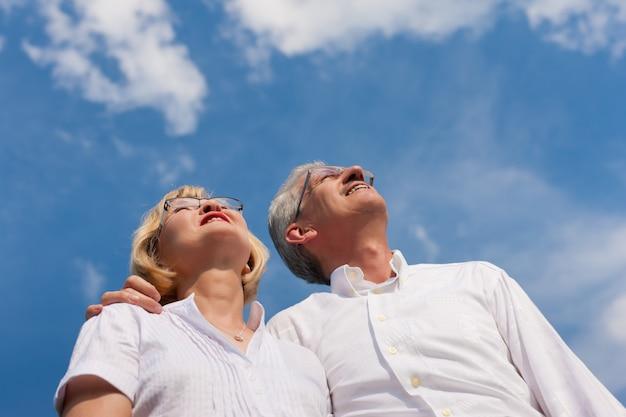 Lächelnde fällige paare, die den blauen himmel untersuchen Premium Fotos