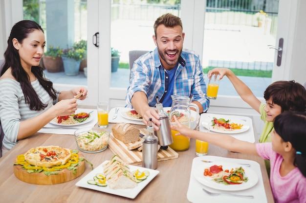 Lächelnde familie, die am speisetische mit lebensmittel sitzt Premium Fotos