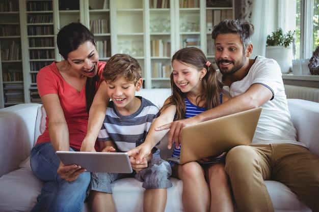 Lächelnde familie, die auf sofa sitzt und auf digitales tablett zeigt Premium Fotos