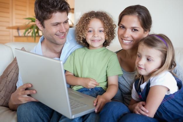 Lächelnde familie, die einen laptop verwendet Premium Fotos