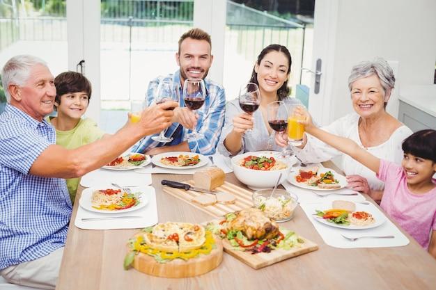 Lächelnde familie, die mit getränkgläsern klirrt Premium Fotos