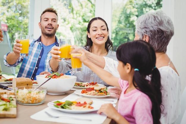 Lächelnde familie, die mit saftglas klirrt Premium Fotos