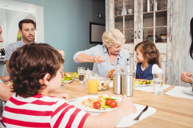 Lächelnde familie mit den großeltern, die am speisetische sitzen Premium Fotos