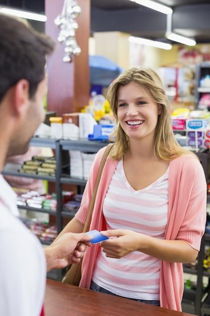 Lächelnde frau an der registrierkasse, die mit kreditkarte zahlt Premium Fotos