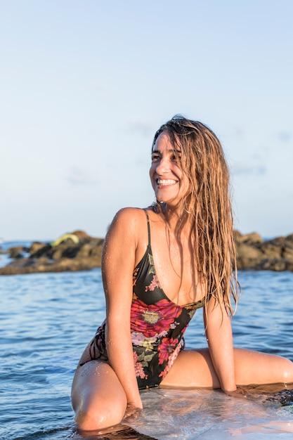 Lächelnde frau auf dem surfbrett, das weg schaut Kostenlose Fotos