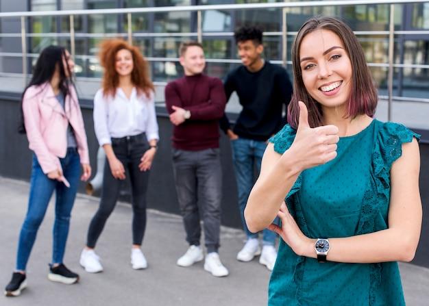 Lächelnde frau der junge, die daumen herauf die geste betrachtet kamera zeigt, während ihre freunde, die unscharfen hintergrund stehen Kostenlose Fotos