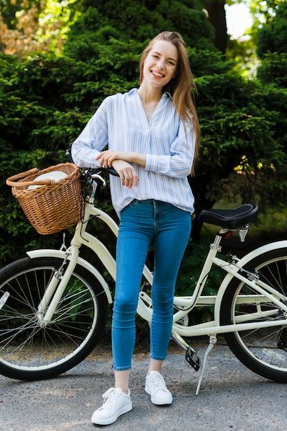 Lächelnde frau der vorderansicht mit fahrrad Kostenlose Fotos