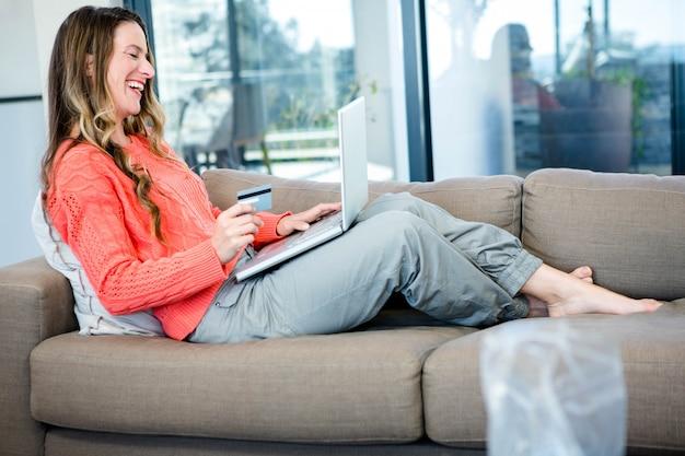 Lächelnde frau, die auf der couch auf ihrem laptop mit ihrer kreditkarte liegt Premium Fotos