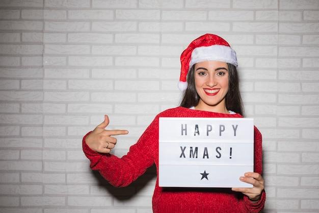Lächelnde frau, die auf glückliches weihnachtszeichen zeigt Kostenlose Fotos
