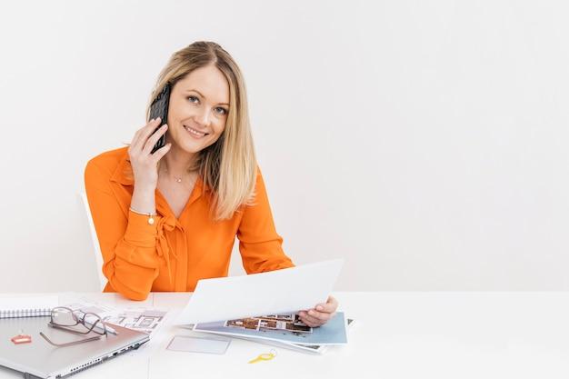 Lächelnde frau, die auf smartphone mit dem halten des weißbuches am arbeitsplatz spricht Kostenlose Fotos