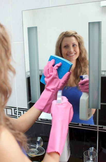 Lächelnde frau, die badezimmerspiegel reinigt Premium Fotos