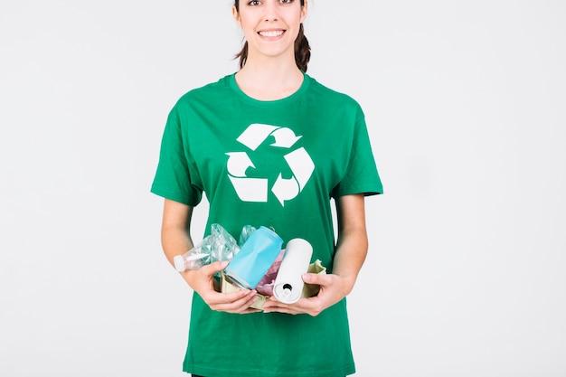 Lächelnde frau, die blechdosen und plastikflaschen hält Kostenlose Fotos