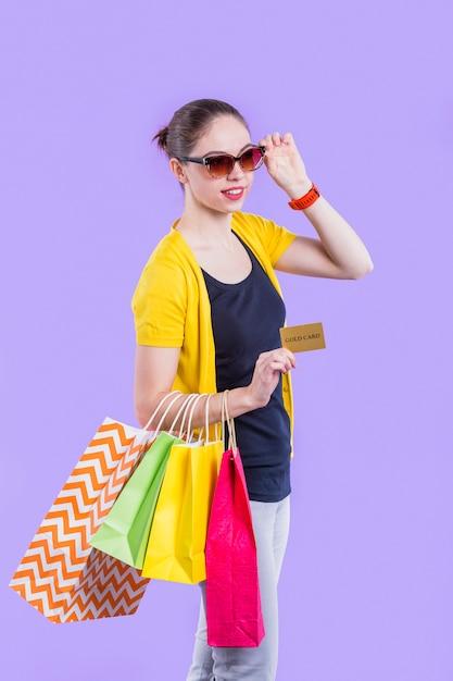 Lächelnde frau, die bunte einkaufstasche mit dem halten der goldkarte auf purpurroter tapete trägt Kostenlose Fotos