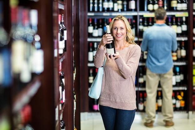 Lächelnde frau, die flasche wein hält Premium Fotos