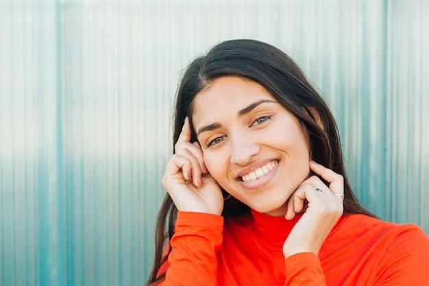 Lächelnde frau, die gegen gewellte wand aufwirft Kostenlose Fotos
