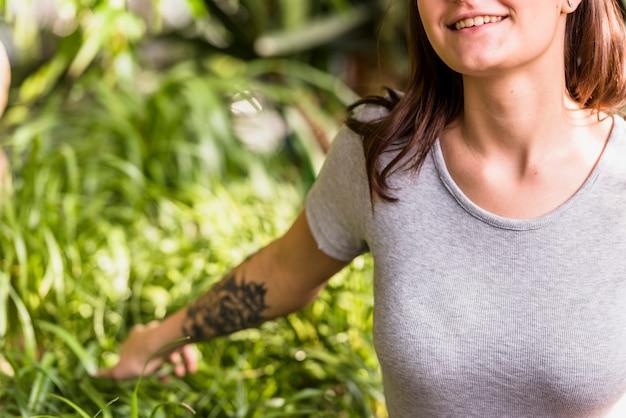 Lächelnde frau, die grüne blätter von anlagen hält Kostenlose Fotos